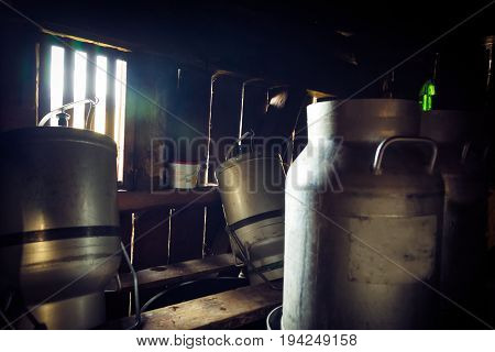 milk cans stacked in a dark room.