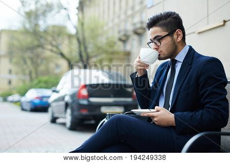Pensive businesman having coffee in urban environment