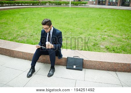 Businessman with touchpad and glass of coffee sitting by green lawn in the city
