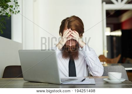 Tired businesman sitting in front of laptop with his head in hands