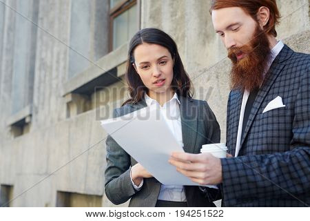 Young economists discussing papers in urban environment