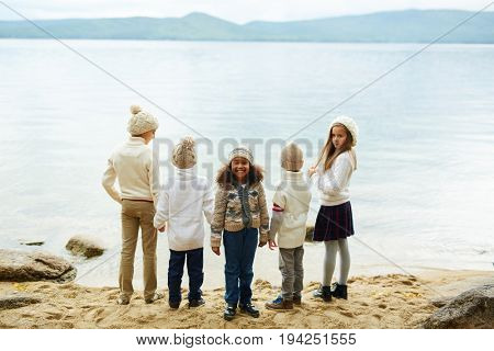 Group of children playing outdoors in nature standing by lake with backs to camera, only one cute African-American girl facing camera and smiling joyfully