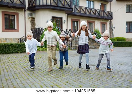 Group of happy children playing outdoors and running towards camera holding hands, all wearing similar knit clothes on warm autumn day