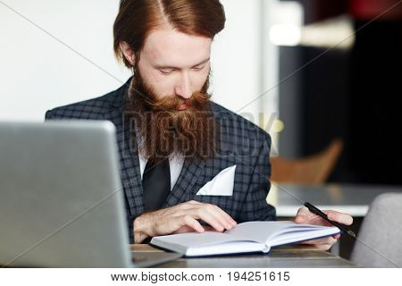 Young trader reading his notes in notebook