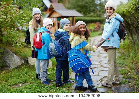 Group of happy children going to school on sunny autumn day, holding hands and looking back at camera smiling