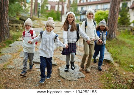 Group of cheerful children running towards camera holding hands on their first school day in September