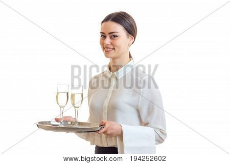 charming waitress in a white shirt smiling and holding two glasses of wine on a tray that is isolated on a white background