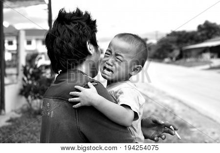 VANG VIENG LAOS - AUGUST 9: B-W photo of Unidentified man and crying child at the side of the road on August 92015 in Vang Vieng Laos