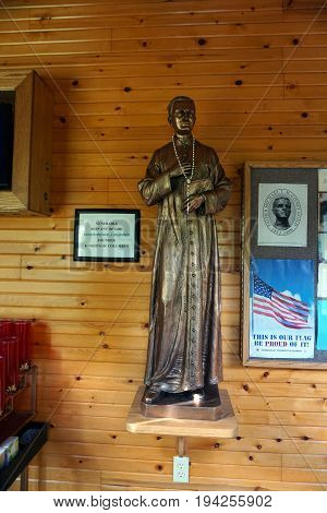 INDIAN RIVER, MICHIGAN / UNITED STATES - JUNE 18, 2017: A sculpture of Father Michael McGivney, founder of the Knights of Columbus, stands in the Cross in the Woods Roman Catholic National Shrine.