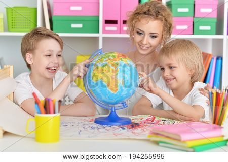 Mother and sons looking at colorful world globe