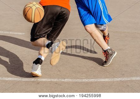 basketball player action on open air court playing with the ball on a bright sunny day - motion blur on hand and ball