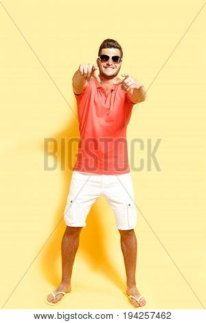 Brunette handsome guy pointing at camera with both hands wearing sunglasses.