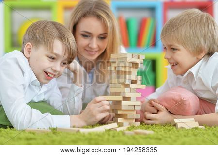 Beautiful young mother and two sons playing with wooden blocks