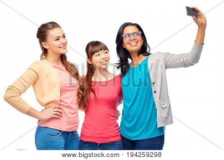 diversity, race, ethnicity and people concept - international group of happy smiling different women over white taking selfie with smartphone