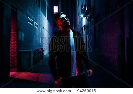 Cool man in sunglasses standing on empty alley at night.