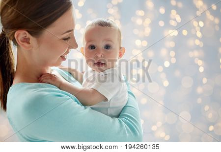 family, motherhood and parenthood concept - close up of happy smiling young mother with little baby over lights background