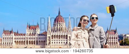 tourism, childhood and travel concept - happy girls taking picture with smartphone on selfie stick over house of parliament in budapest