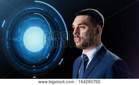 business, people and technology concept - businessman in suit with virtual projection over black background