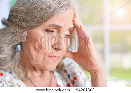 Senior woman with headache holding hand on forehead