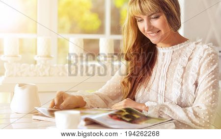 Young woman sitting at kitchen table with cup of tea and reading magazine