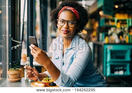 Smiling Young African Woman Working Online By A Cafe Window