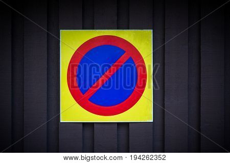 No parking sign. Prohibition symbol. Sign indicating warning and forbidden. Grunge shabby paper sticker isolated on dark wooden background.