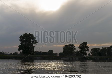 River running across with reflections in the water. Evening  sunset with pink and violets colors in the sky. Silhouettes