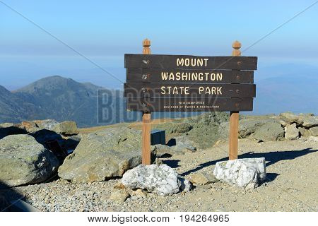Mount Washington State Park sign in fall with foliage from summit of Mount Washington, White Mountains, New Hampshire, USA.