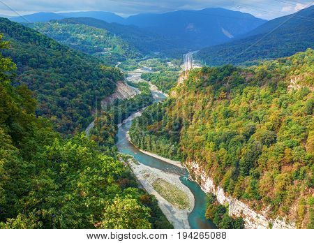 Beautiful view on park hills forest and green mountains, river rafting on yellow boats with tourists. Russia Sochi best holidays vacation tour. Sochi adler SKYPARK metal bridge. National park