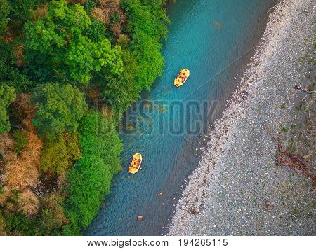 Diagonal view from above on river rafting on yellow boats with tourists sportsmen without helmets. Rafting holidays vacation in Sochi. Rafting boats. Rafting people