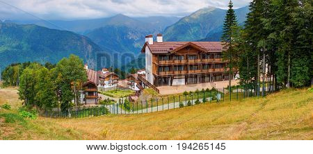 Panoramic view on Swiss cottage chalet style wooden architecture hotels among green mountains hills in Krasnaya Polyana near to Adler and Sochi. Russia holidays vacation tours ski and mountain bike