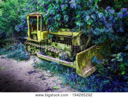 Old fashion antique worn rusted construction full track crawler yellow tractor among green trees. Hue construction industry machine crawler tractor blade vehicle. Abstract tractor background texture