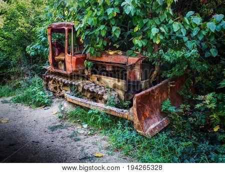 Old fashion antique worn rusted construction full track crawler red tractor among green trees. Old agricultural industry machine crawler tractor blade vehicle. Abstract tractor rusted metal beast