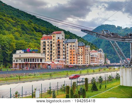 SOCHI, RUSSIA, SEP, 10, 2015: View on Rosa Khutor colorful hotels modern buildings for tourists cable way funicular among green hills. Dramatic sky. Sochi Roza Khutor holidays vacation bike ski tours