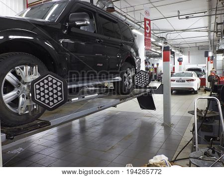 MOSCOW, MAR,02, 2017: Car automobile wheel alignment maintenance works repair at automotive service center workshop. Technical maintenance wheel alignment correction fixation MOT. Car maintenance