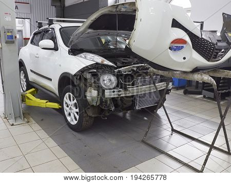 MOSCOW, MAR,02, 2017: Car automobile maintenance works repair MOT at automotive service center workshop. Engine repair maintenance. Car bodyshell repair fixation MOT. Car maintenance