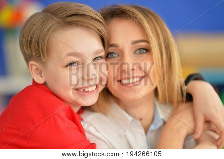 Smiling mother and son looking at camera