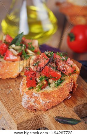 Italian bruschetta with chopped tomatoes basil herbs and olive oil on grilled crusty bread. Italian cuisine concept.