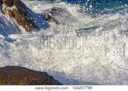 Seawater spray over the stones on the beach