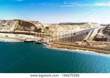 In the in August 2015 newly opened Eastern Expansion Canal of the Suez Canal with a view of the excavated sand masses and an access road to a ferry dock