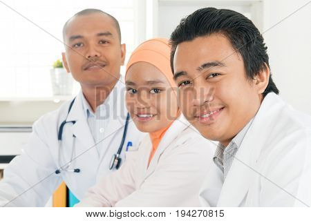 Portrait of medical team sitting in hospital office, Southeast Asian Muslim doctors and nurses.