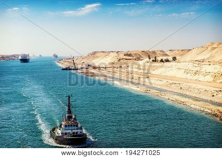 The Suez Canal - a ship convoy passes through the new eastern extension canal opened August 2015 a tugboat in the foreground