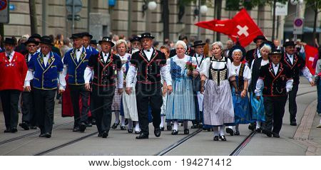 ZURICH - AUGUST 1: Swiss National Day parade on August 1, 2011 in Zurich, Switzerland. People in historical costumes marching on the Bahnhofstrasse in Zurich