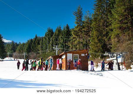 Bansko, Bulgaria - February 19, 2015:Skiers at the draglift in Bansko, Bulgaria.  Ski lift, pine trees and mountains view