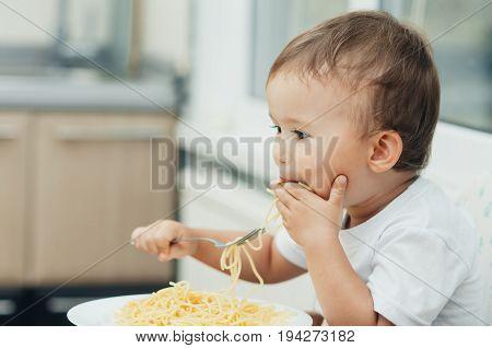 The Child Greedily Eating Pasta