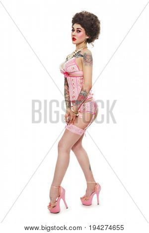 Young beautiful gothic pin-up girl in pink corset and stockings over white background