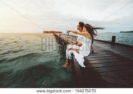 Woman in white long dress is showing to her friend something on horizon during beautiful sunset on Maldives island while they both sitting on wooden bridge and smiling ocean villas in background