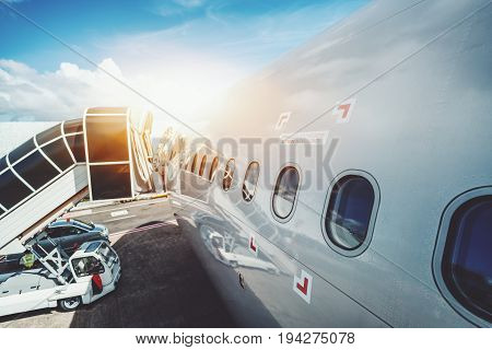 Wide angle shooting of contemporary white airplane body with numerous windows and boarding ramp staying on maintenance in airport of Male on sunny day with staff car near it