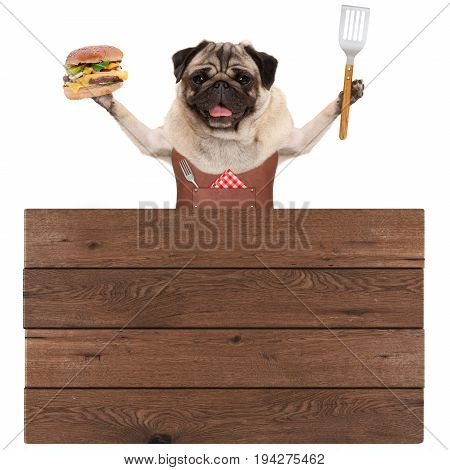 happy pug dog wearing leather barbecue apron holding hamburger and spatula with wooden board sign isolated on white background