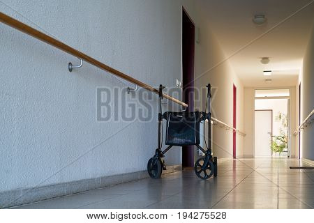 MAGDEBURG, GERMANY - JUNE 12, 2017: long dark hallway and rollator in a dreary nursing home for old people in Magdeburg.